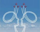 stock photo of partnership  - Teamwork management concept as a group of acrobatic jet airplanes creating smoke shaped as two people working together in partnership for a successful coordinated organization for success - JPG