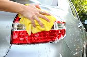 picture of tail  - a man wash the tail light at car wash shop - JPG
