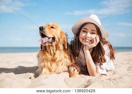 Portrait of cheerful beautiful young woman lying with her dog on the beach