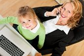 Family Business - telecommuter Businesswoman and mother with kid on her lap is making a phone call,