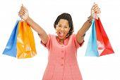 Mulher afro-americana entusiasmada segurando em seus sacos de compras.  Isolado no branco.