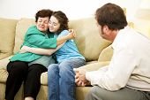 Mother and daughter hugging during a family counseling session with a therapist.