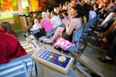 Voting device lies on knee in auditorium on television broadcast