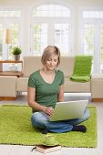 Smiling woman sitting on floor at home in living room using laptop computer for teleworking.?