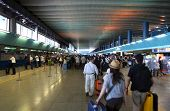 FIUMICINO, ITALY - AUGUST 6: Crowd people in passageway for registration inside Leonardo da Vinci-Fiumicino Airport - largest airport in Italy on August 6, 2010 in Fiumicino near Rome, Italy.