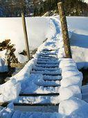 Bridge over river ander snow in caucasus mountain