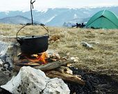 Campfire,kitchenware and tent in camping