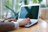 Pessoa digitando em um laptop moderno em um escritório