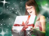 Beautifull girl opening x-mass magic present. Christmas