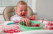 Naughty Messy Dirty Baby Is Eating With Hands. poster