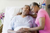 stock photo of hospital patient  - Senior Couple Embracing In Hospital - JPG