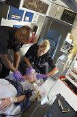 image of cpr  - Paramedics performing CPR on patient in ambulance - JPG
