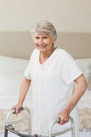 stock photo of zimmer frame  - Senior woman with her zimmer frame - JPG