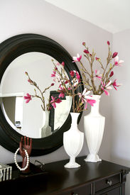 picture of flower vase  - A dresser with flowers inside a home interior - JPG