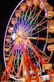 A rainbow colored Ferris wheel at night