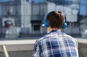 Back View Of Young Man In Checkered Shirt With Wireless Headphones Looking At Cityscape. Guy Listeni poster
