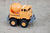 Plastic Toy Orange Color For Construction.by Mix Cement Car On Cement Floor. poster