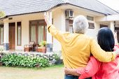 Elderly man pointing to a comfortable residential house while standing close to his wife poster