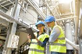 Industrial engineers working in recycling plant with tablet poster