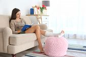 Young Woman With Broken Leg In Cast Reading Book While Sitting On Sofa At Home poster