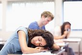 Student sleeping on her desk in a classroom