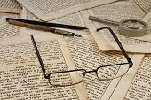 Glasses, pencil, ink  pen and lens on old book pages