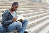 Young Serious African-american Man Reading Book, Sitting On Campus Stairs, Studying And Preparing Fo poster