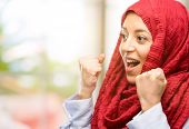 Young arab woman wearing hijab happy and excited expressing winning gesture. Successful and celebrat poster