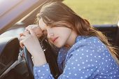 Exhausted Overworked Female Driver Can`t Drive Car Any More, Naps On Wheel, Feels Sleepy And Tired,  poster