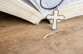 Closeup Christian Cross And Bible On Old Wooden Table With Sunlight. Christian Concept Jesus Is The  poster