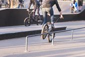Two Cyclists On Bmx Bikes Do Tricks In A Park Skate. Bike Skater Slides On Bmx By Perel. Training Of poster