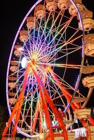 stock photo of amusement park rides  - A rainbow colored Ferris wheel at night at a Fair - JPG
