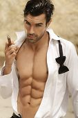 stock photo of stud  - Sexy male model smoking cigar in open formal attire exposing great toned muscular body and abs - JPG