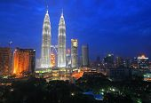 stock photo of klcc  - Petronas Twin Towers and buildings in the city centre of Kuala Lumpur at dusk.