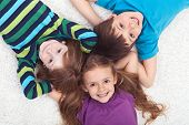 Three kids laying on the floor together - childhood friendship