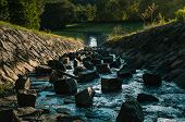 Photo Of Strong Water Stream With Stones And Big Rocks Inside Flowing From Reservoir (dam) In The Hi poster