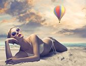 Beautiful woman lying on a beach with hot-air balloon in the background