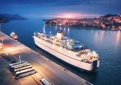 Aerial View Of Cruise Ship In Port At Sunset. Landscape With Ships And Boats In Harbour, City Lights poster