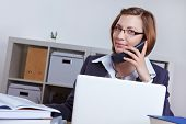 Smiling female laywer in office talking on the phone