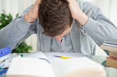 stock photo of midterm  - Student tearing his hair doing his homework - JPG