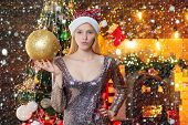 Young Beautiful Woman Decorating Christmas Tree With Bauble - New Year Tradition. Woman In Christmas poster