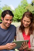 Man and his friend smiling as the watch something on a tablet in a sunny park
