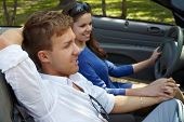 Young couple sits in a cabriolet hand in hand, girl is on a driver seat, focus on a boy face