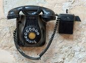 Vintage black Bakelite telephone fixed to a wall