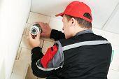 video surveillance service. Technician installing camera poster