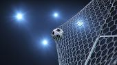 Soccer Ball Flew Into The Goal. Soccer Ball Bends The Net, Against The Background Of Flashes Of Ligh poster