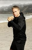 Beach portrait of an active young athlete in boxing stance with fists up