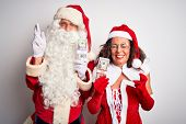 Senior couple wearing Santa Claus costume holding dollars over isolated white background gesturing f poster