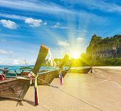 Long tail boats on tropical beach in Thailand oin sunset