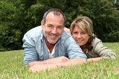 pic of 55-60 years old  - Senior couple having fun laying in grass - JPG